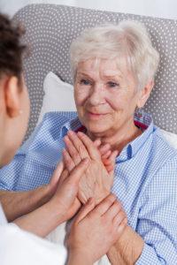 Vertical view of nurse comforting elderly woman